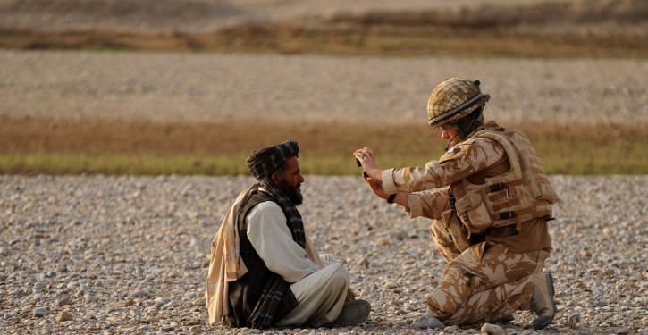 A British troop assigned to Royal Air Force II Squadron takes a photo of an Afghan detainee for biometric purposes, June 26, 2010, Dand District Kandahar, Afghanistan. RAF II Squadron partnered with the Afghan National Army 205th Corps and Afghan National Police to perform a joint patrol through local villages in search of insurgents, weapons caches and illegal drugs. As a result, three insurgents were found and detained, along with several pounds of marijuana. (U.S. Air Force photo by Senior Airman Kenny Holston)(Released)