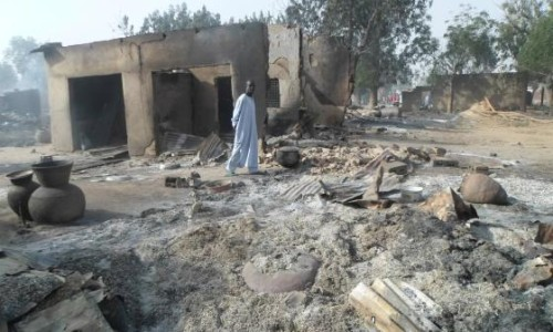A man walks past burnt out houses following an attack by Boko Haram in Dalori village near Maiduguri, Nigeria, Jan. 31, 2016. Jossy Ola—AP